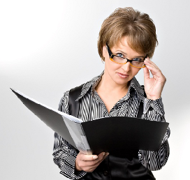 A woman holding a book, looking over her glasses